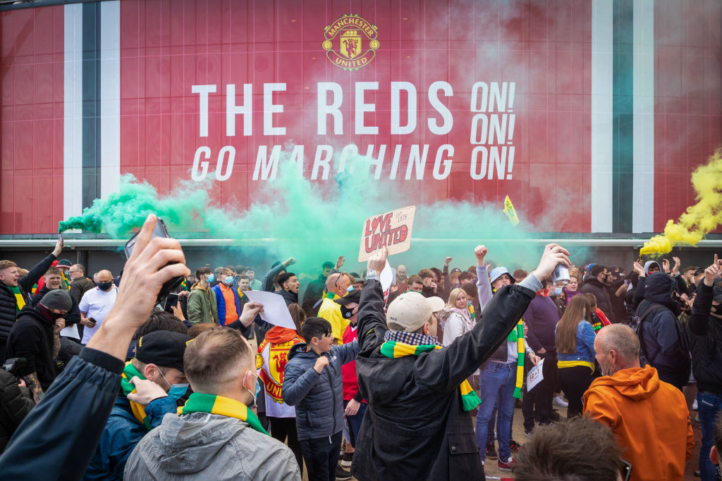 Football fans gather in Old Trafford to protest against the